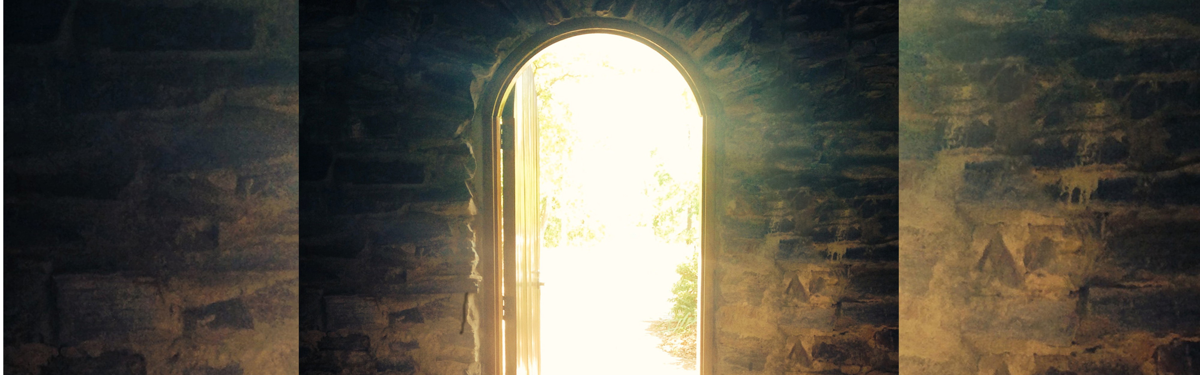 open door to the outside with a glow from the sun