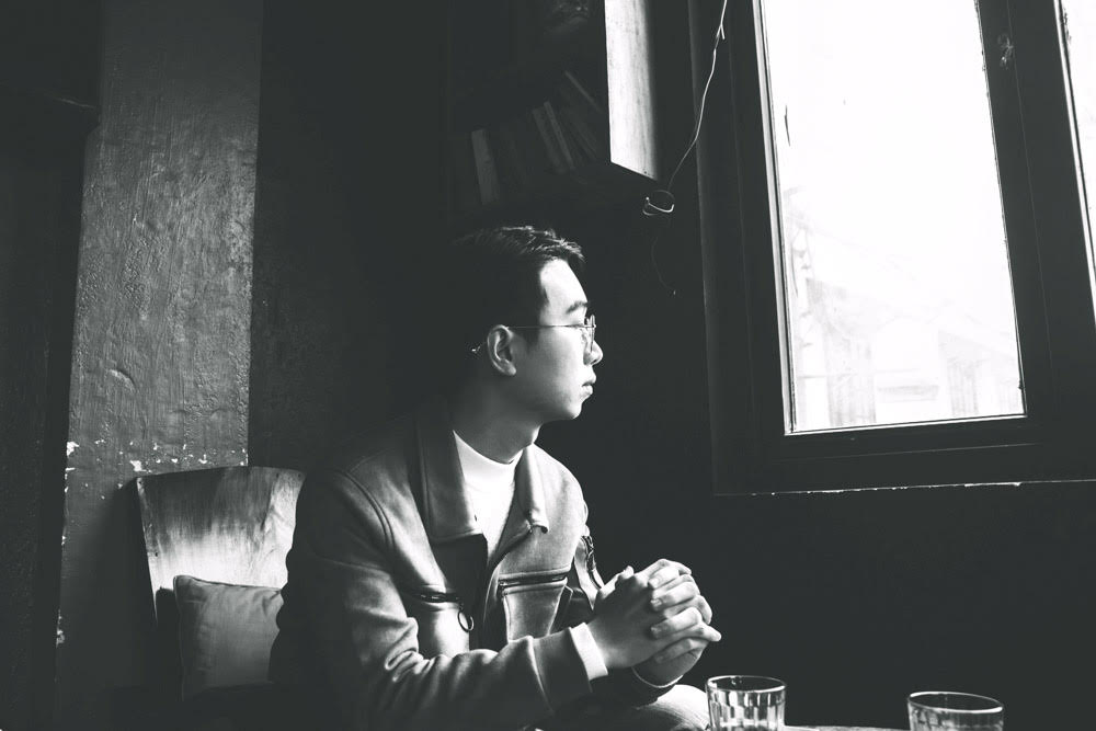 Young man with hands folded, looking out the window.