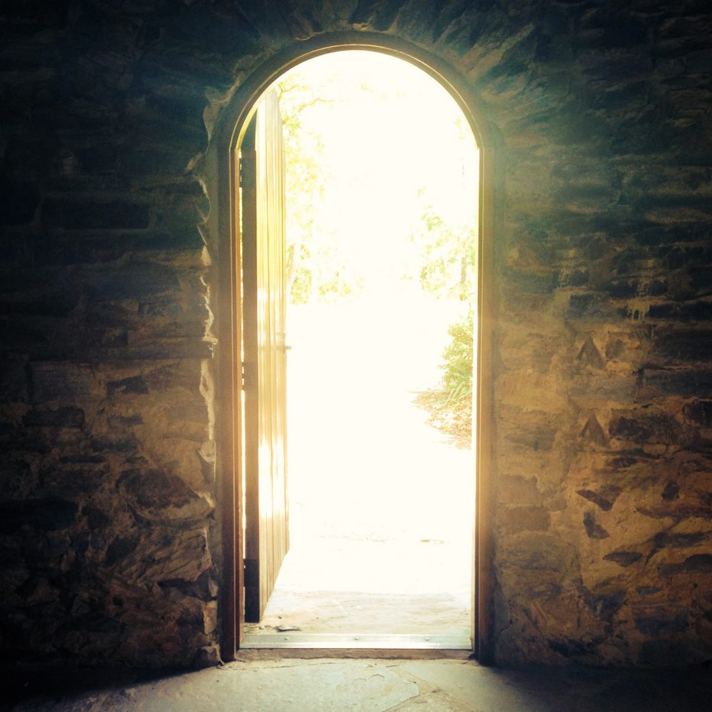 Open door with a glow of light through it from the outside